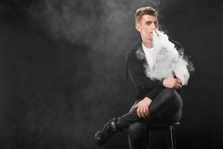 Young bearded man exhaling smoke of electronic cigarette surrounded by clouds of steam Stock Photo