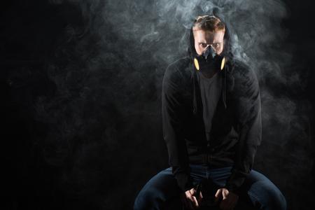Man wearing protective filter mask smoking electronic cigarette
