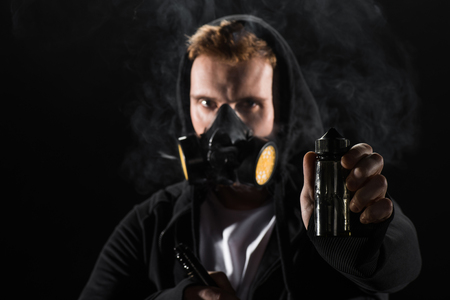 Man wearing protective filter mask smoking electronic cigarette showing E-liquid Reklamní fotografie