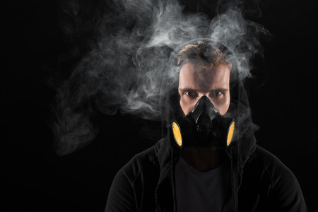Man in black hood wearing protective filter mask surrounded by clouds of smoke Stock Photo