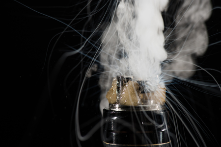 Activating electronic cigarette with clouds of smoke on dark background 版權商用圖片