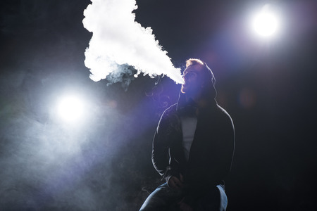 Young bearded man exhaling smoke of electronic cigarette against backlit Reklamní fotografie