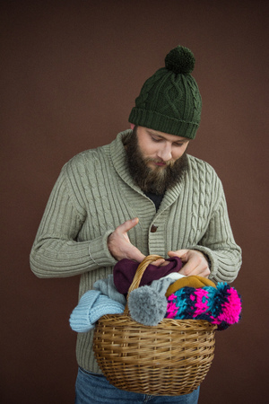 man holding wicker basket with pile of hats and scarfs isolated on brown