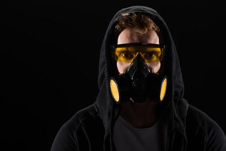 Man in black hood wearing protective glasses and filter mask isolated on black Stock Photo