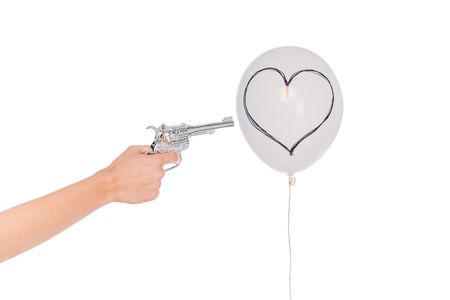 cropped shot of hand holding revolver and shooting balloon with heart symbol isolated on white 写真素材