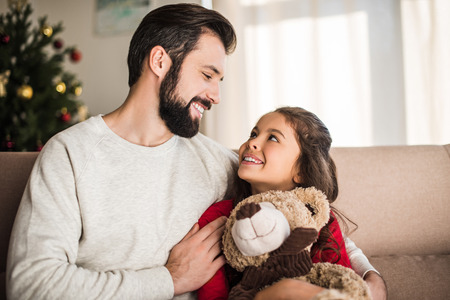 father hugging daughter with teddy bear Stock Photo
