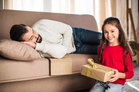 daughter holding gift box while father sleeping on sofa 版權商用圖片