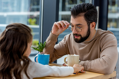 father and daughter sitting in cafe with cups of cacao with marshmallow
