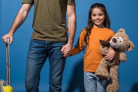bijgesneden afbeelding van dochter en vader permanent en hand in hand op blauw Stockfoto