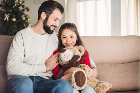 smiling father hugging daughter with teddy bear