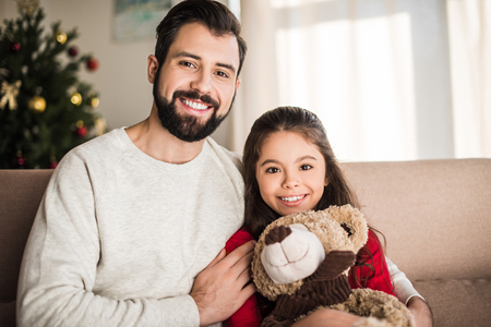 father hugging daughter with teddy bear and looking at camera 版權商用圖片