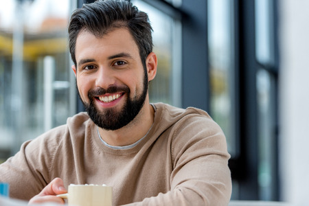 smiling handsome man holding cup of coffee with marshmallow and looking at camera Stock Photo