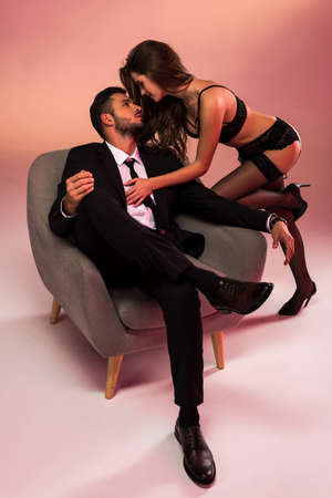 successful businessman sitting on armchair with sexy girl in lingerie
