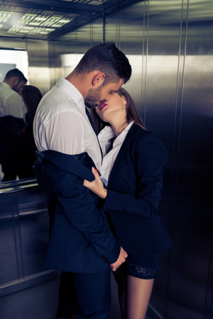 sensual business couple undressing in elevator Stock fotó