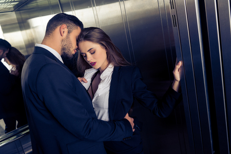 sensual business couple undressing in elevator 写真素材
