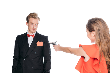 young woman with revolver shooting at boyfriend with red heart symbol isolated on white