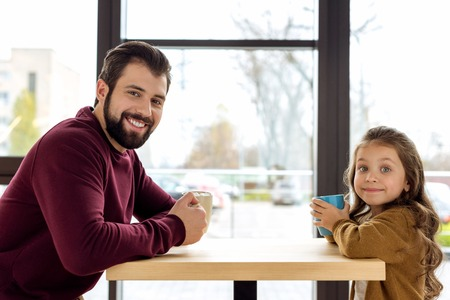 father and daughter holding cups and looking at camera Stock Photo
