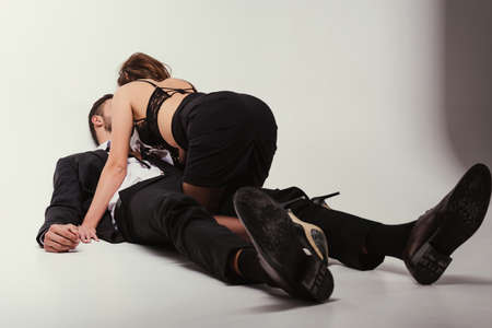 young handsone businessman with beautiful girl in skirt and lingerie lying on floor Standard-Bild