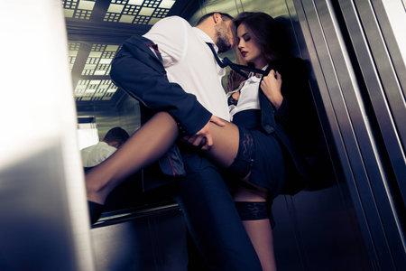 エレベーターで服を脱ぐ官能的なビジネスカップル