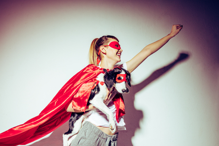 side view of smiling woman and little puppy in superhero costumes Stock fotó