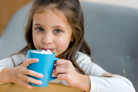 adorable kid drinking cacao with marshmallow in cafe Stock Photo