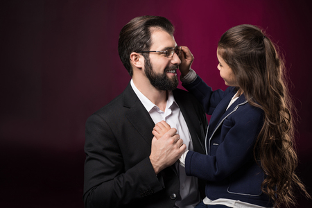 daughter fixing father glasses on burgundy Stock Photo