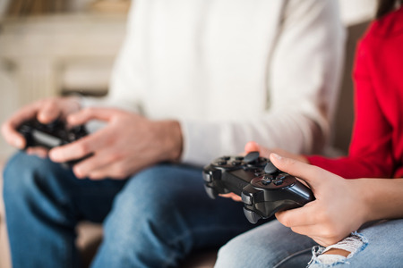 cropped image of father and daughter holding game pads
