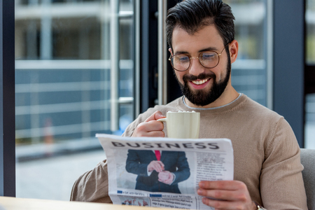 smiling man drinking coffee with marshmallow and reading business newspaper