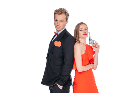 stylish young couple in suit and red dress standing with revolver and looking at camera isolated on white