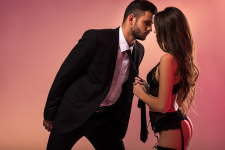 beautiful girl in lingerie holding necktie of businessman Stock Photo