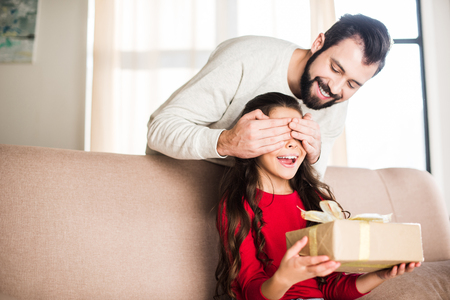 smiling father covering daughter eyes from back and presenting gift