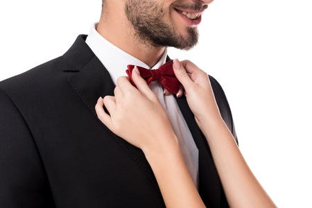 cropped image of girlfriend fixing boyfriends tie bow isolated on white Banco de Imagens