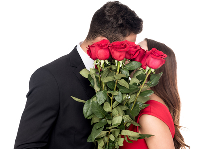 heterosexual couple kissing and covering faces with bouquet isolated on white Stockfoto