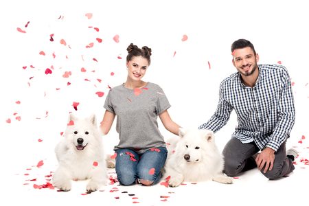 couple sitting with dogs under falling confetti isolated on white, valentines day concept