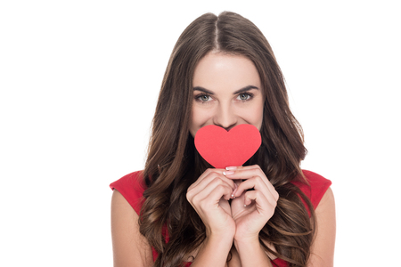 smiling girl covering mouth with paper heart isolated on white, valentines day concept