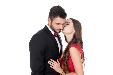 side view of girlfriend kissing boyfriends cheek isolated on white Stock Photo