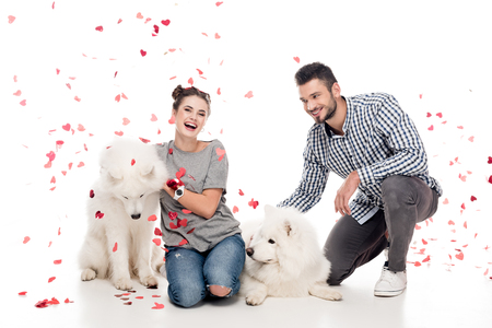 couple sitting with dogs under falling confetti on white, valentines day concept