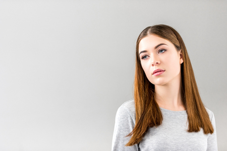 portrait of pensive young woman looking away isolated on grey Stockfoto - 104832379