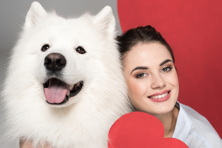 smiling girl with white dog and paper heart on white, valentines day concept Stock Photo