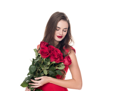 attractive girl standing with bouquet of red roses isolated on white