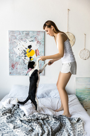 side view of young woman and puppy dancing on bed together in morning Archivio Fotografico