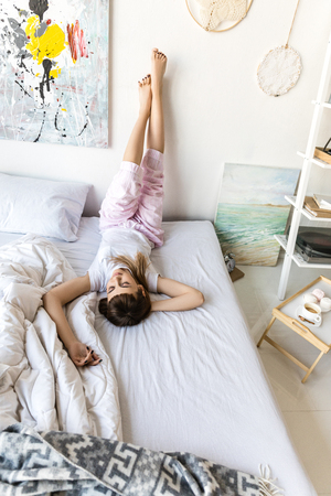 young woman in pajamas resting on bed in morning at home
