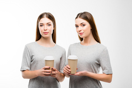 portrait of beautiful twins with coffee to go in hands looking at camera isolated on white Foto de archivo