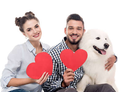 happy couple with samoyed dog and paper hearts isolated on white, valentines day concept Stock Photo