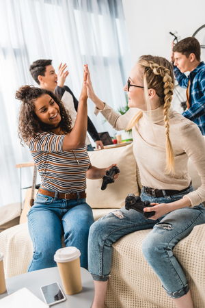 multiethnic girls giving high five for winning boys in video game