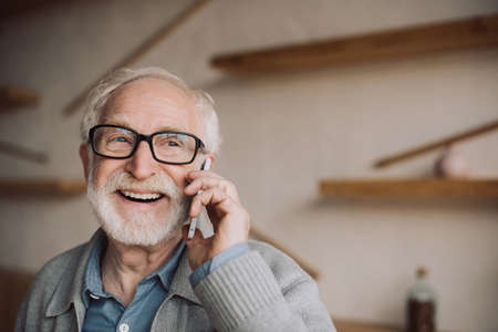 gelukkig bebaarde senior man praten via de telefoon
