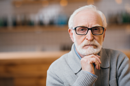 close-up portrait of thoughtful senior man looking at camera Imagens