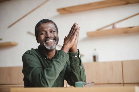 lächelnder reifer Afroamerikanermann, der im Café sitzt