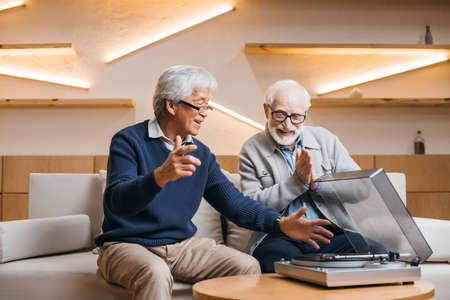 happy senior friends listening vinyl record while sitting on couch Banque d'images - 104848753
