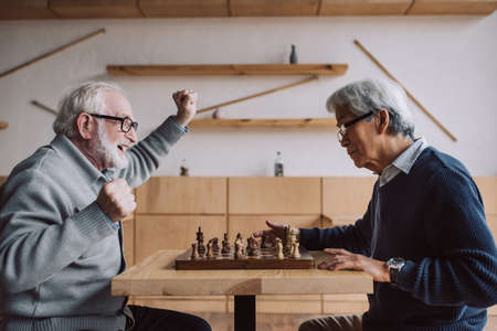 side view of senior multiethnic men playing chess Stock Photo